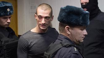 Russian artist Pyotr Pavlensky (C), accused of vandalism after torching the doors to the headquarters of the FSB security service, the successor to the KGB, the previous day, is escorted into a courtroom during his trial in Moscow on November 10, 2015. AFP PHOTO / DMITRY SEREBRYAKOV        (Photo credit should read DMITRY SEREBRYAKOV/AFP/Getty Images)