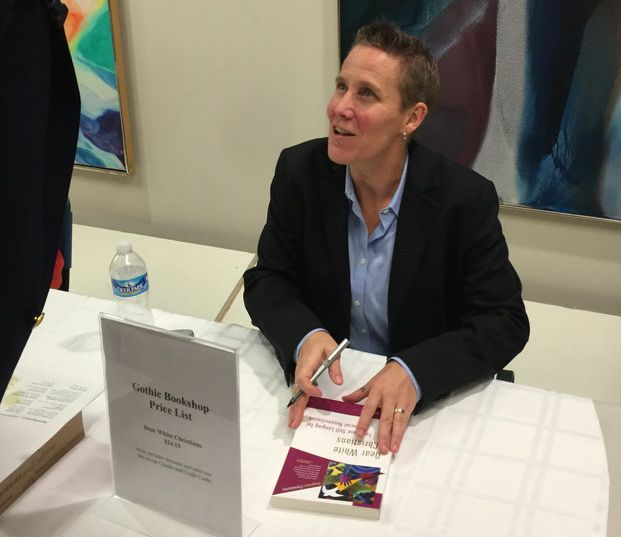 "Drake University ethicist Jennifer Harvey, signs her book ""Dear White Christians,"" during the Race & Faith Dialogue serie"