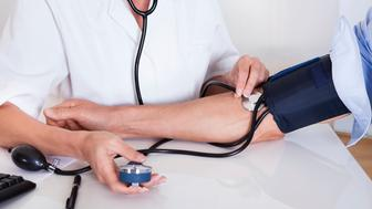 Attractive young female doctor or nurse taking a male patients blood pressure using a sphygmomanometer