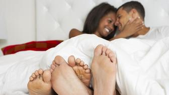 Couple Relaxing In Bed Wearing Pajamas With Feet Out At The Bottom Smiling At Each Other