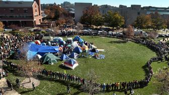 University of Missouri students circle tents on the Carnahan Quadrangle, locking arms to prevent media from entering the space following the resignation of President Timothy W. Wolfe on Monday, Nov. 9, 2015. (Robert Cohen/St. Louis Post-Dispatch/TNS via Getty Images)