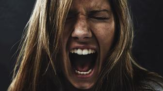 A young woman screaming uncontrollably while isolated on a black background