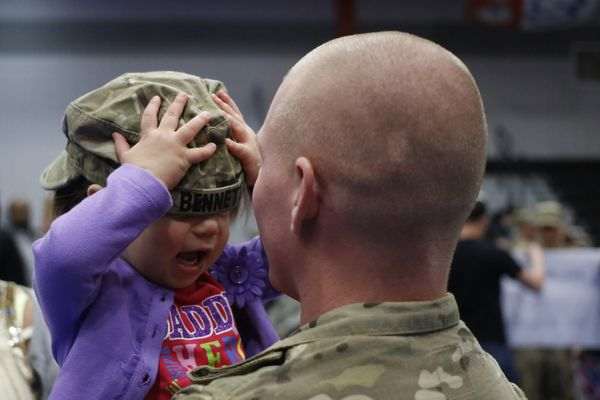 Spc. Brian Bennett of the U.S. Army's 3rd Brigade Combat Team, 1st Infantry Division, holds his 2-year-old daughter Sophia fo