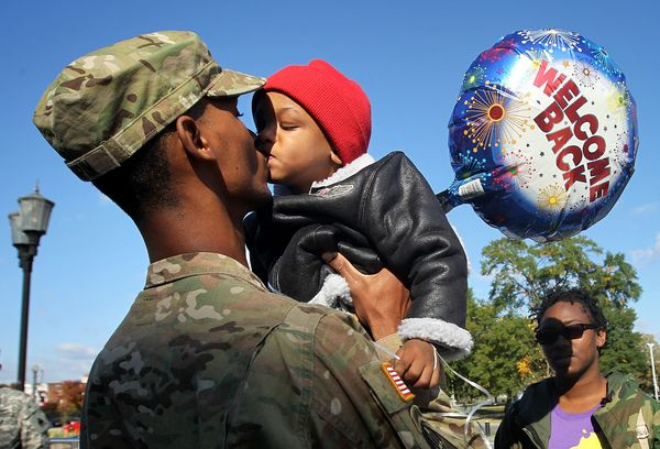 Spc. Marqes Turpin of the 273rd Military Police Company of DC Army National Guard kisses his two-year-old son Josiah Turpin a