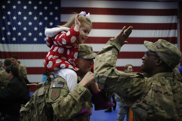 Three-year-old Bella Hanley high fives Sgt. Frank Passmore while sitting atop her dad Spc. Jeffrey Hanley of the U.S. Army's