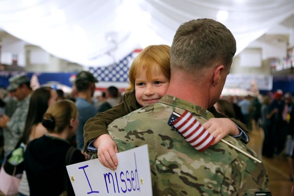 Five-year-old Gavin Shaw flashes a smile as he hugs his father, Master Sgt. Adam Shaw, during a Welcome Home Ceremony for app