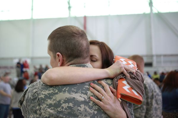 Warrant OfficerAnthony Woodmansee of the U.S. Army's 101st Airborne Division is embraced by his wife Emily Woodmansee d