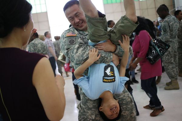 Lt. Col. Sung Kato of the U.S. Army's 101st Airborne Division gives his son an upside-down hug during a homecoming ceremony a