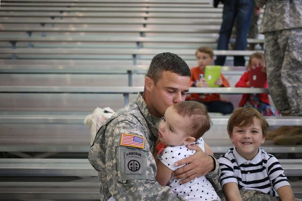 Maj. Dave Armeson of the U.S. Army's 101st Airborne Division kisses his daughter Adelyn Armeson, 2, during a homecoming cerem