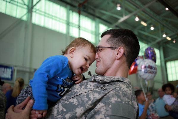 Staff Sgt. Chris Oldham of the U.S. Army's 101st Airborne Division plays with his son Isaac Oldham during a homecoming ceremo