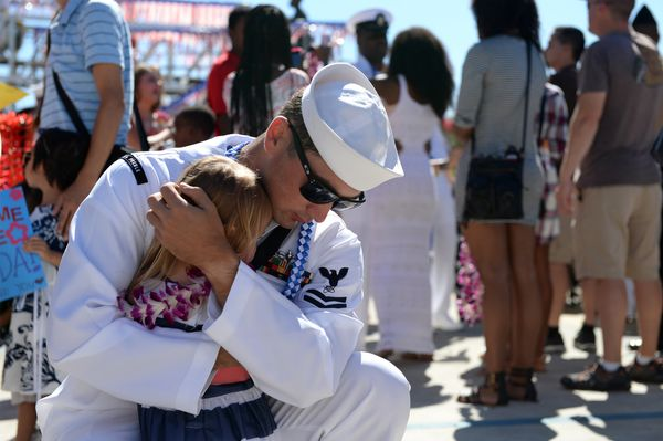 Electronics Technician 2nd Class James Whatley embraces his daughter during a homecoming ceremony at Joint Base Pearl Harbor-