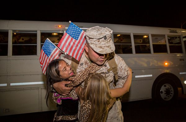 Chief Petty Officer Curtis A. Harmon, leading petty officer, regimental aid station, 7th Marine Regiment, hugs his daughters,
