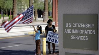 Protesters stand outside The U.S. Citizenship and Immigration Services building Saturday, May 1, 2010 in Phoenix to protest Arizona's controversial new immigration bill. (AP Photo/Matt York)