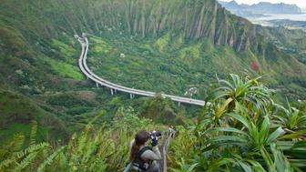 The hike up the Stairway to Heaven is also known as Haiku Stairs. It is one of the most popular trails in Oahu young woman taking photo.