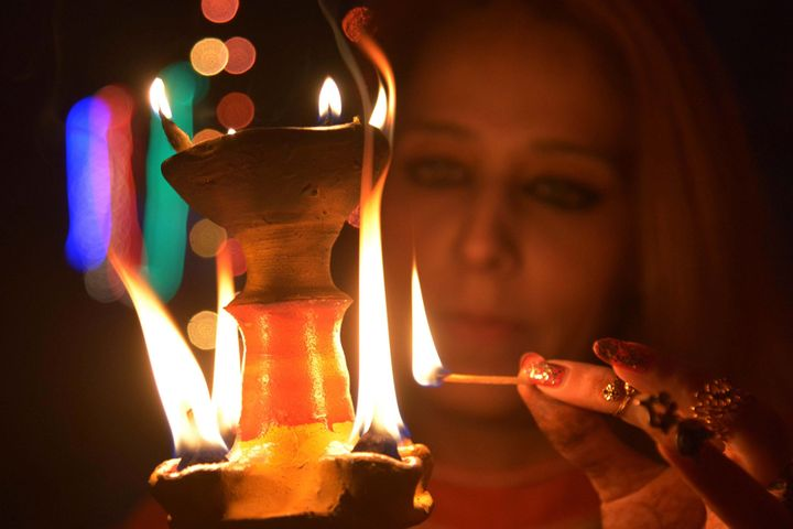An Indian woman lights an earthen lamp in Amritsar on November 10, 2015 on the eve of the Indian festival of Diwali.