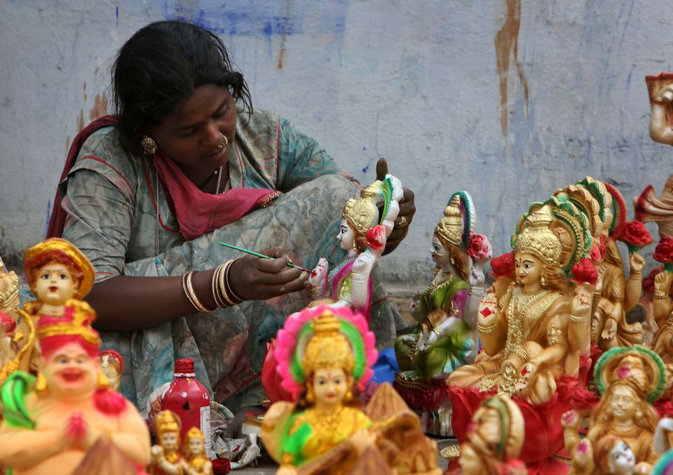 An artist gives final touches to idols of Hindu Goddess Lakshmi, the Goddess of wealth, ahead of Diwali, the festival of ligh