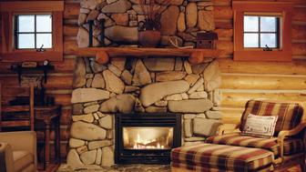 Armchair beside stone fireplace in log cabin