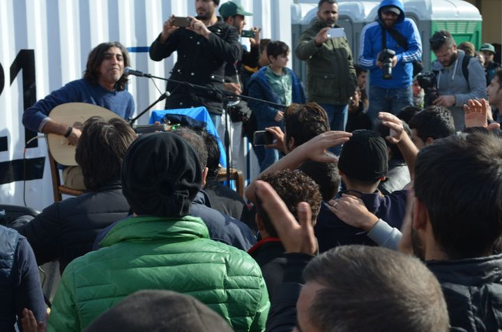 Syrian musician Ziad Rajab plays to a crowd at the Idomeni camp.