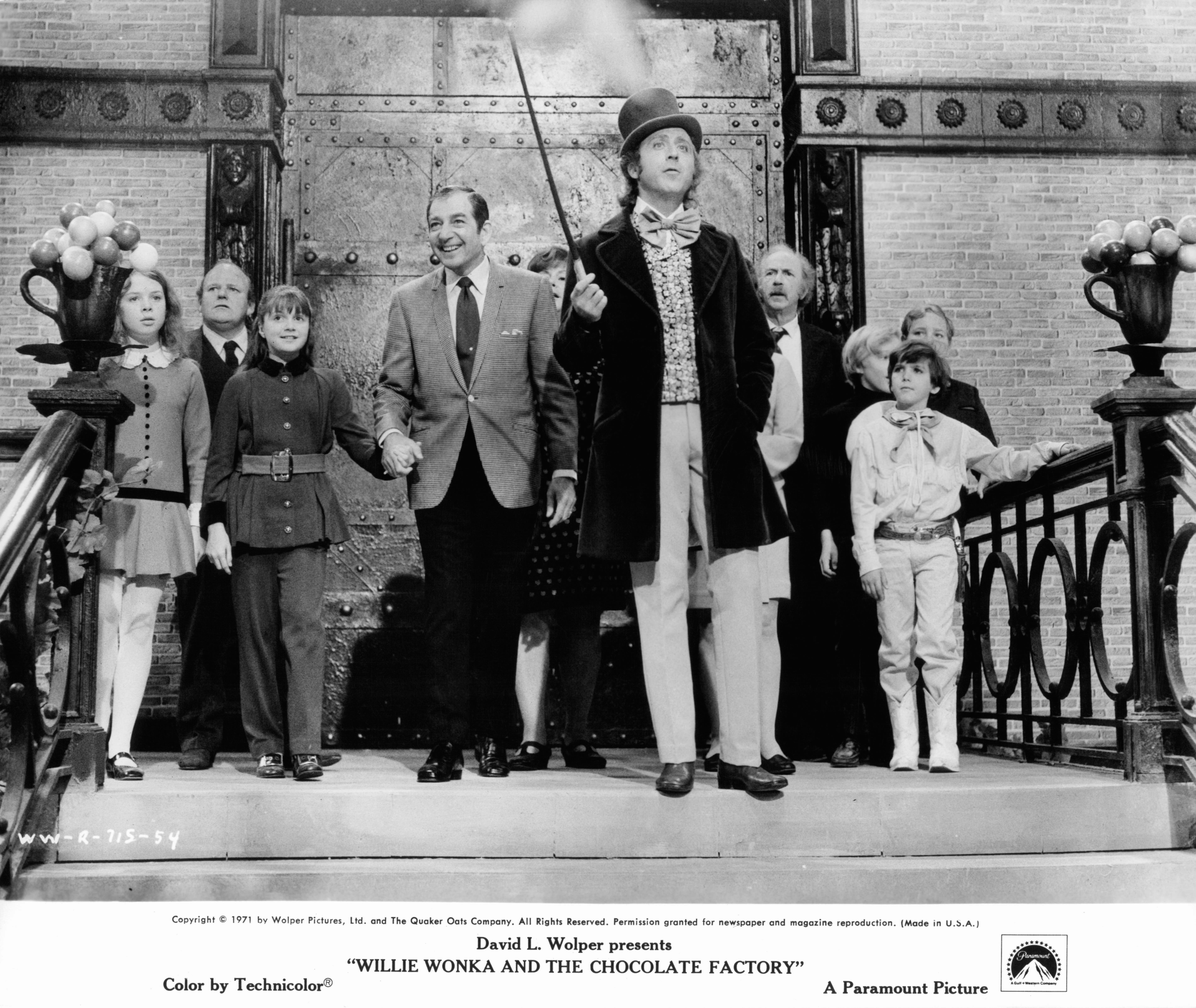 Julie Dawn Cole, Roy Kinnear, Denise Nickerson, Leonard Stone, Ursula Reit, Gene Wilder, Jack Albertson, Peter Ostrum, Paris Themmen, and Michael Bollner at top of staircase in a scene from the film 'Willy Wonka & the Chocolate Factory', 1971. (Photo by Paramount/Getty Images)