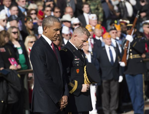 President Barack Obama pauses for the playing of 'Taps' as he participates in a wreath laying ceremony at the Tomb of the Unk