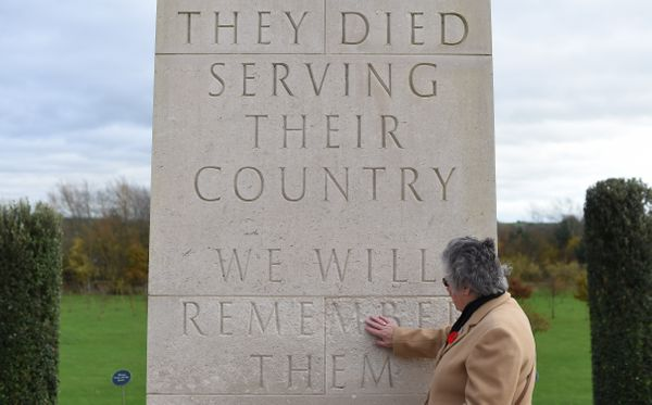 A woman touches a memorial plaque after the Armistice Day service of remembrance with members of the armed forces and veteran
