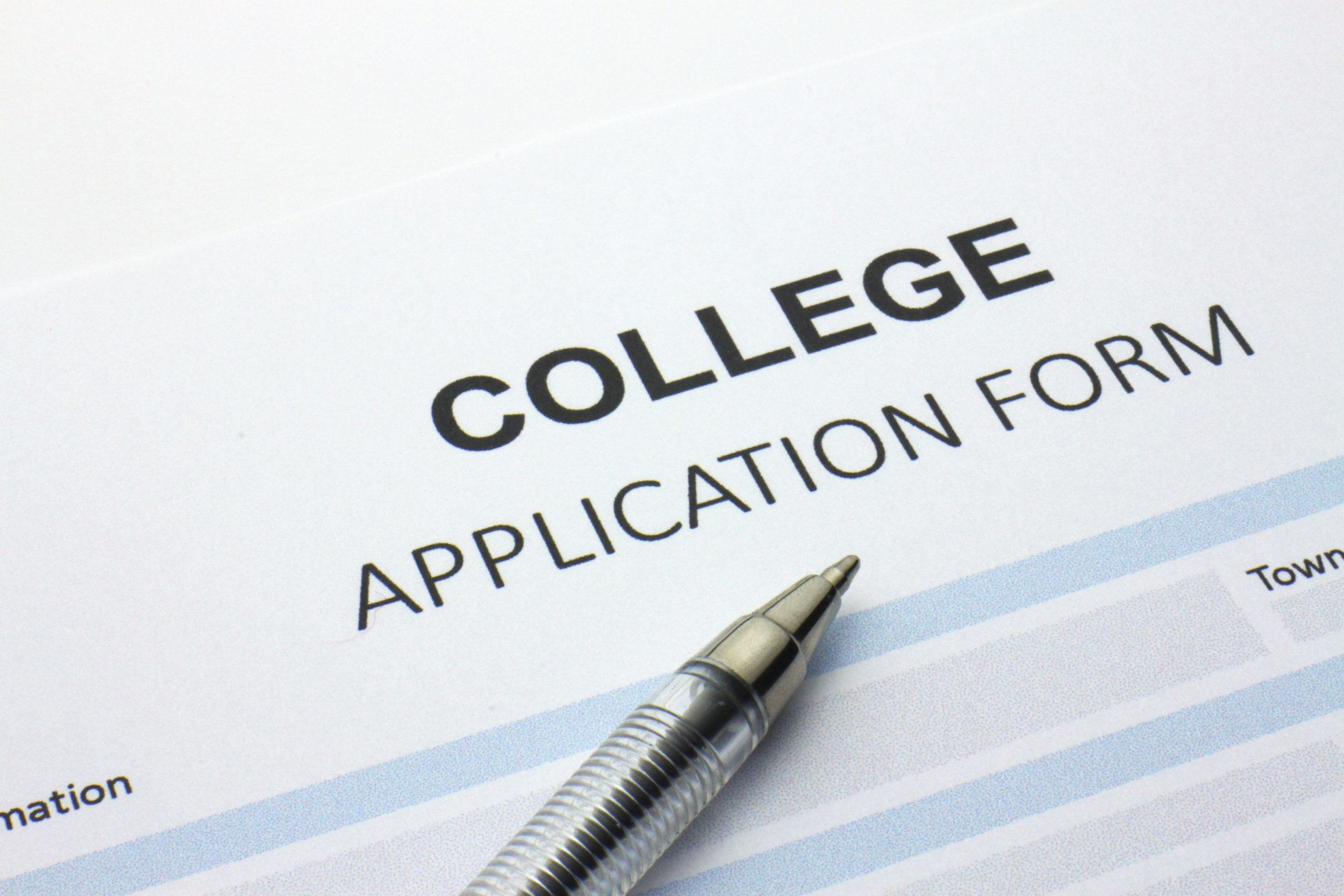 A blank college application form with pen resting across it.