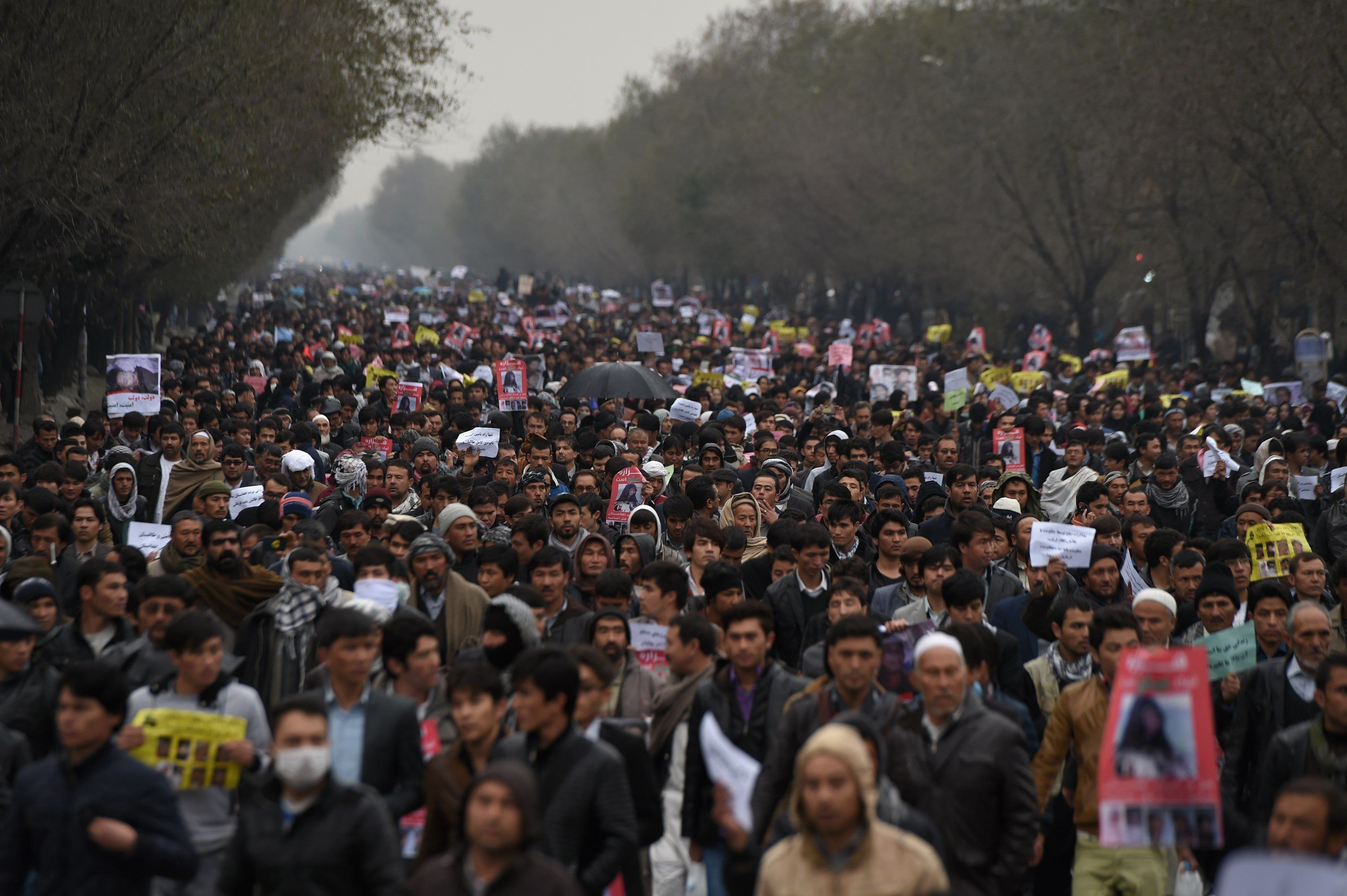 Afghan protesters march during a demonstration, over the killing of seven Shiite Hazaras, in Kabul on November 11, 2015. Thousands of protesters marched coffins containing the decapitated bodies of seven Shiite Hazaras through the Afghan capital Kabul on November 11 to demand justice for the gruesome beheadings, which prompted fears of sectarian bloodshed in the war-torn country. Demonstrators gathered in the rain in west Kabul and marched towards the city centre, chanting death slogans to the Taliban and the Islamic State group while demanding justice and protection from the government. AFP PHOTO / SHAH Marai        (Photo credit should read SHAH MARAI/AFP/Getty Images)