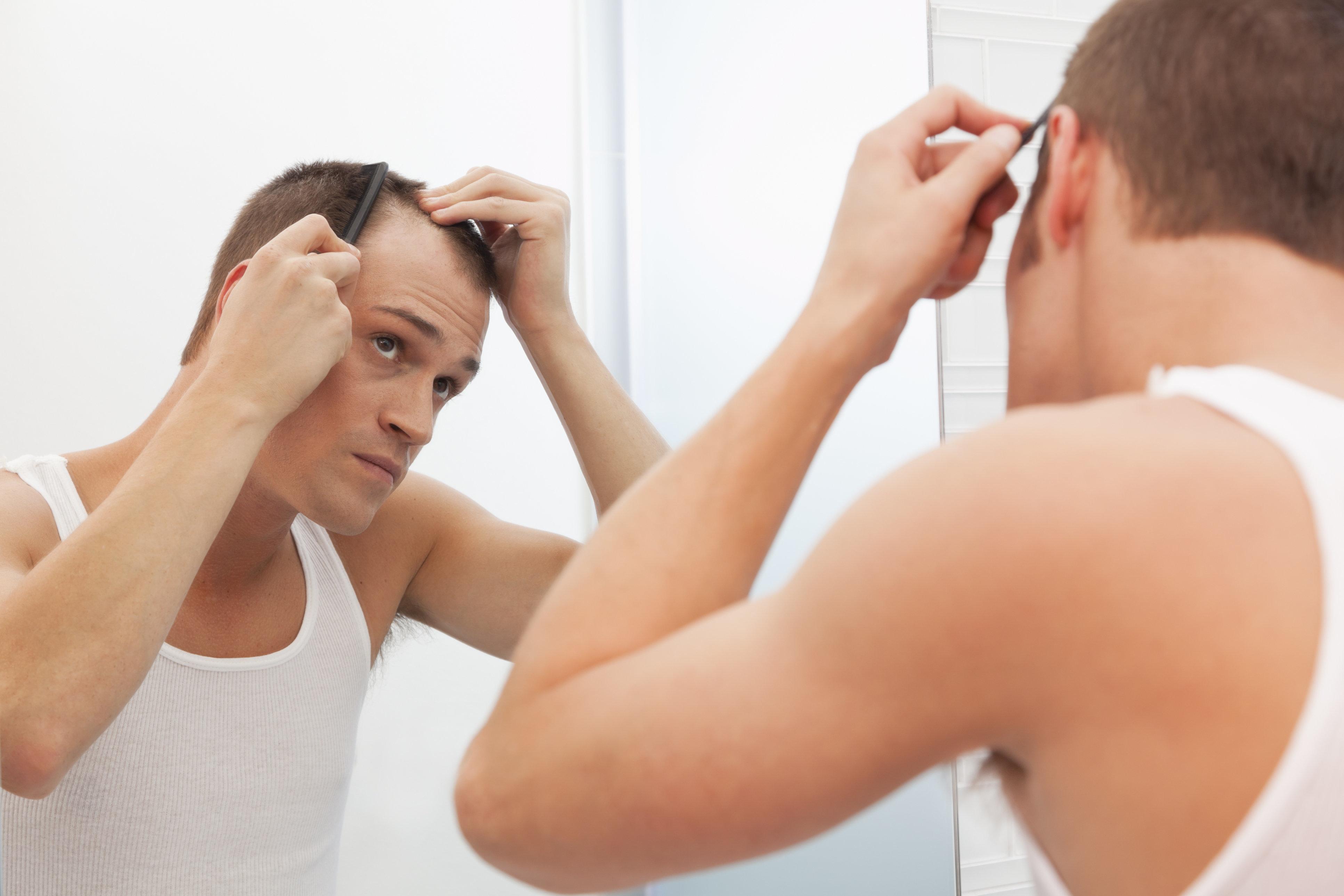 USA, Illinois, Metamora, Man combing hair in front of mirror