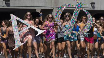 The University of Alabama's Alpha Phi sorority runs out of BryantDenny Stadium screaming with excitement during Bid Day on Saturday, Aug. 16, 2014, in Tuscaloosa, Ala. (AP Photo/Brynn Anderson)