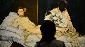 A woman looks at Edouard Manet's 'Olympia' on April 23, 2013 in Venice, during  the 'Manet Return to Venice' exhibition, which runs until 18 August 2013, at the Doge's Palace in Venice. Edouard Manet's 'Olympia' will be appearing alongside the Titian's 'Venus of Urbino' a masterpice of Renaissance and source of ispiration for the French artist. AFP PHOTO / GIUSEPPE CACACE        (Photo credit should read GIUSEPPE CACACE/AFP/Getty Images)