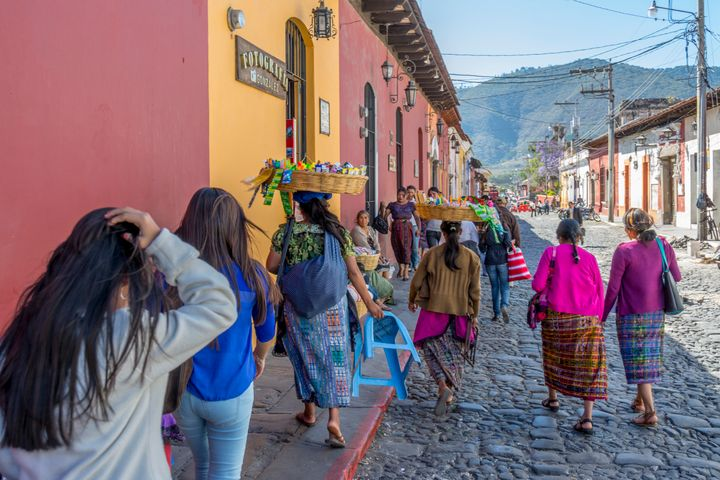 Women carrying baskets on their head while walking down the street in Antigua Guatemala.