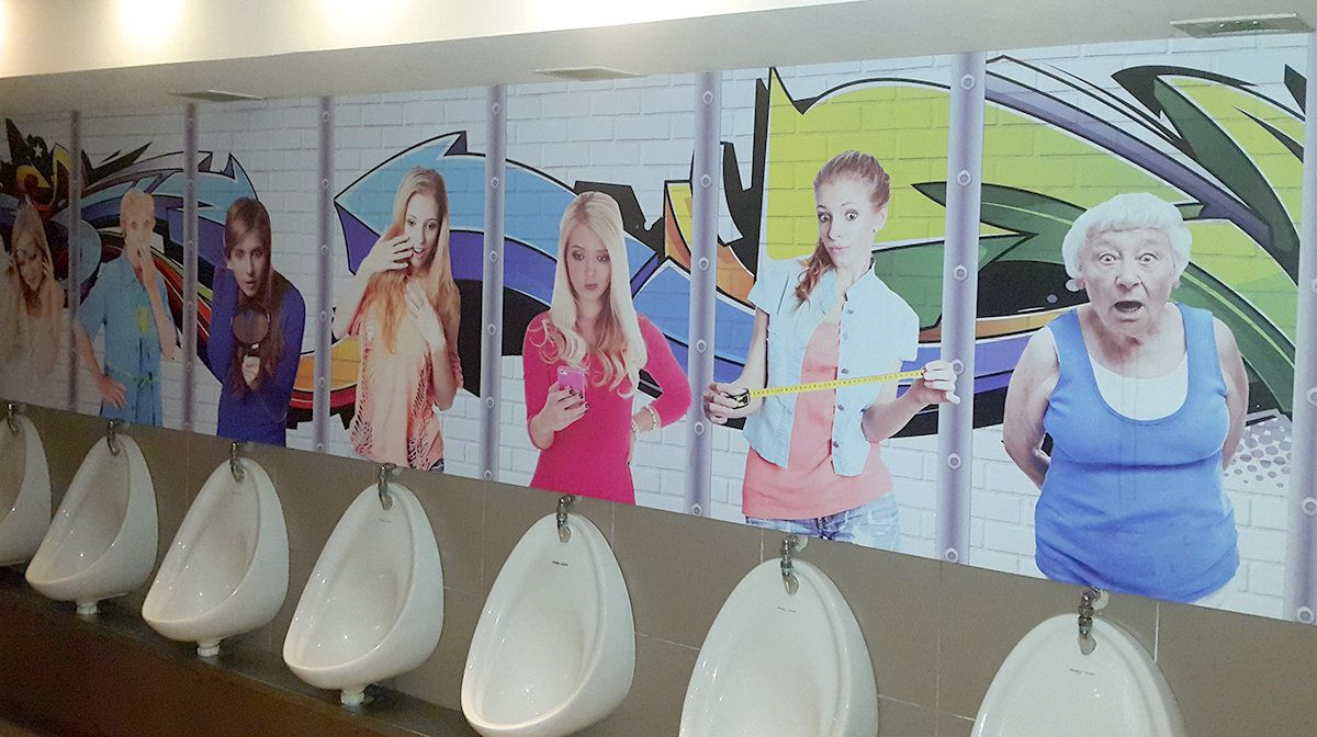 TERI: Women hold mans dick at urinal