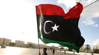 A Libyan man waves his national flag as protesters gather for a demonstration calling on the international community to  lift the ban on arming or munitioning the Libyan army, in the eastern coastal city of Benghazi on February 27, 2015. Benghazi is one of the less stable areas of the North African state, which has been plunged into chaos since the 2011 revolution that toppled dictator Moamer Kadhafi. AFP PHOTO / ABDULLAH DOMA        (Photo credit should read ABDULLAH DOMA/AFP/Getty Images)