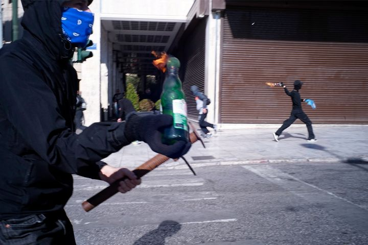 Riotpolice were seen firing tear gas at dozens of black-clad people who hurled petrol bombs and stones and smash shop w