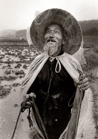 A farmer smiles up at the sky.