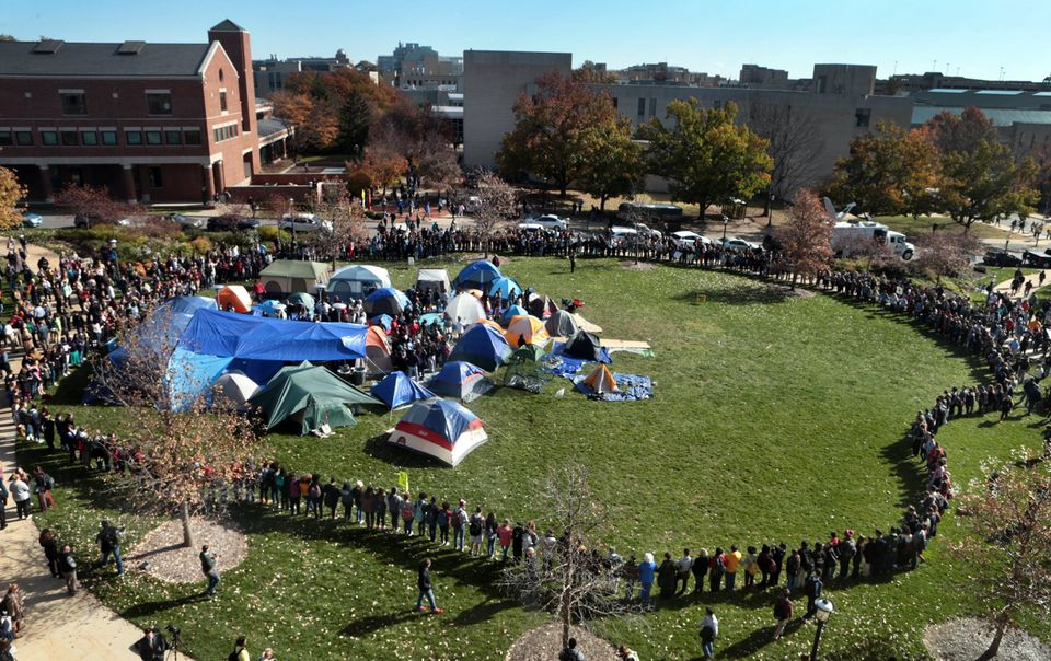 University of Missouri students circle tents on the Carnahan Quadrangle, locking arms to prevent media from entering the spac