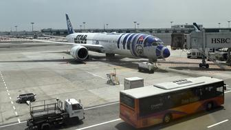 An All Nippon Airways (ANA) Boeing 787 aircraft, painted in special livery of Star Wars character R2-D2, is seen at the Changi International airport in Singapore on November 12, 2015. A promotional event for the Star Wars film franchise was held at Singapore's Changi airport as part of the arrival of an All Nippon Airways (ANA) Boeing 787 aircraft painted in special Star Wars livery in the likeness of popular robot character R2-D2. AFP PHOTO / ROSLAN RAHMAN        (Photo credit should read ROSLAN RAHMAN/AFP/Getty Images)