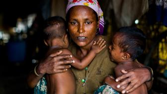SITTWE , MYANMAR - JULY 17 : A distressed mother named Shamijder (age 30) holds onto her twins aged 1 year whom both suffer from malnutrition in Sittwe, Rakhine State Myanmar on July 17 2015. An estimated 110,000 ethnic Rohingya live in an overcrowded IDP camp in the outskirts of Sittwe.  The Rohingya continually make attempts to flee the camps by fishing boat and seek asylum in neighbouring Islamic countries however often fall victim to human traffickers. At current they are a stateless people believed to be illegal immigrants from Bangladesh. According to the UN the Rohingya are one of the most persecuted minorities in the world.  (Photo by Asanka Brendon Ratnayake/Anadolu Agency/Getty Images)