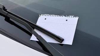blank sheet of paper under a windshield wiper