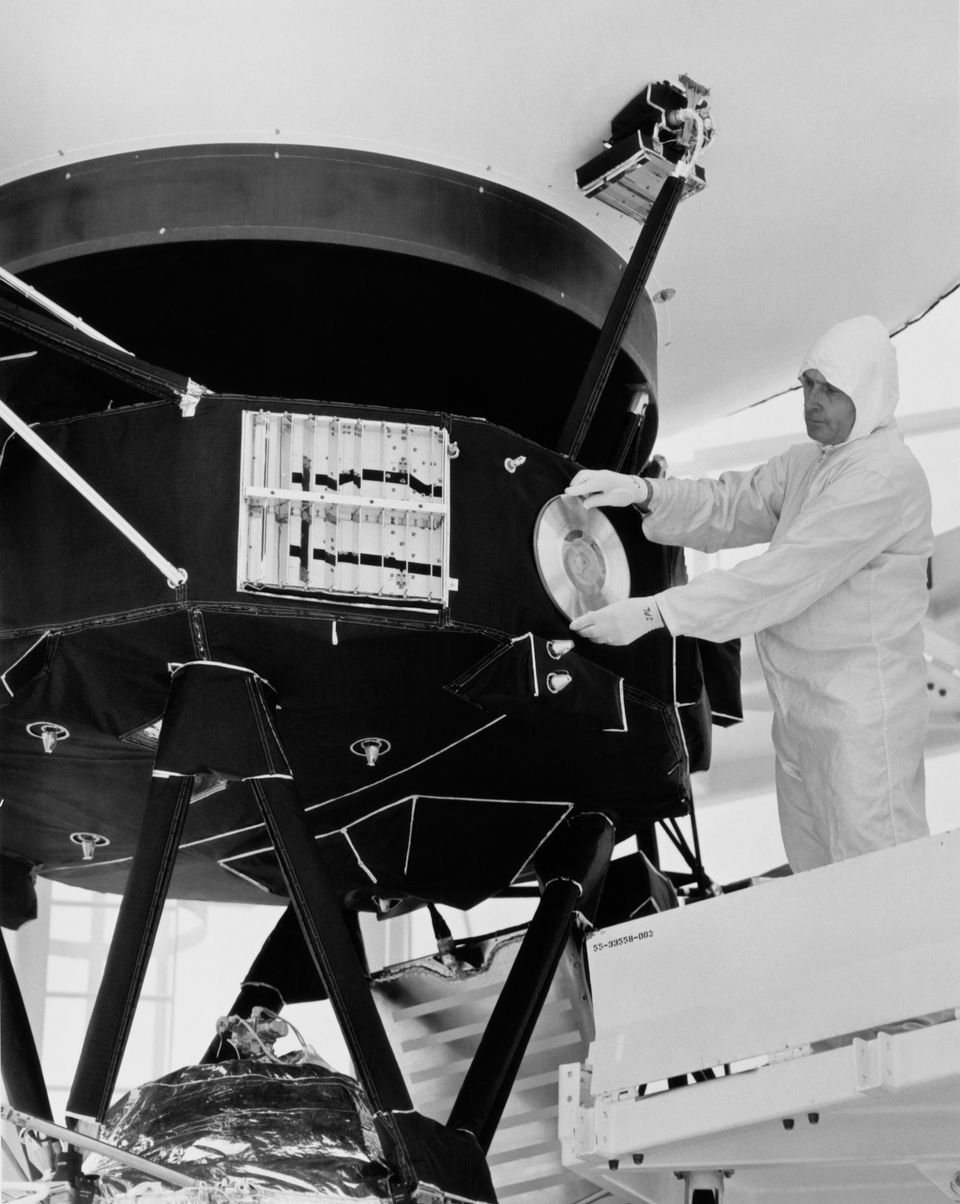 A technician attaches a gold record to a Voyager space probe, circa 1977. Voyager 1 and its identical sister craft, Voyager 2