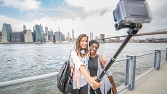 Two female friends taking a picture of New York and Brooklyn Bridge - Best friends traveling and recording their trip with a action camera