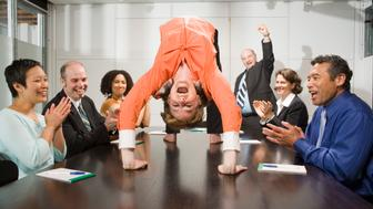 Businesswoman doing backbend at meeting