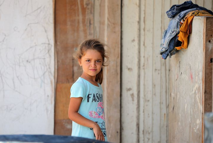 A Syrian refugee girl poses for a photo at an unofficial refugee camp in the northern Lebanese city of Tripoli, north of the