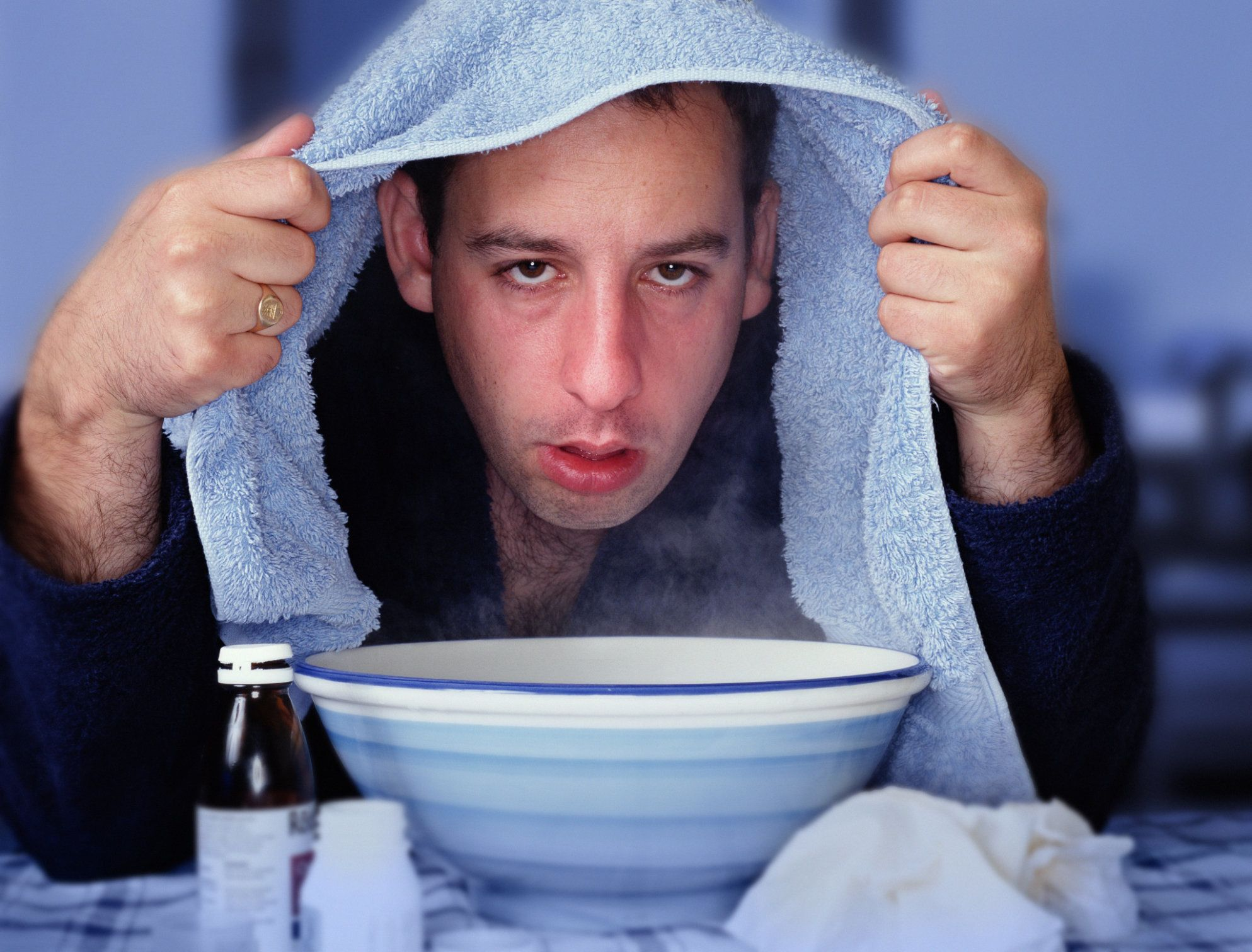Man with towel over head, leaning over bowl of steam (Enhancement)