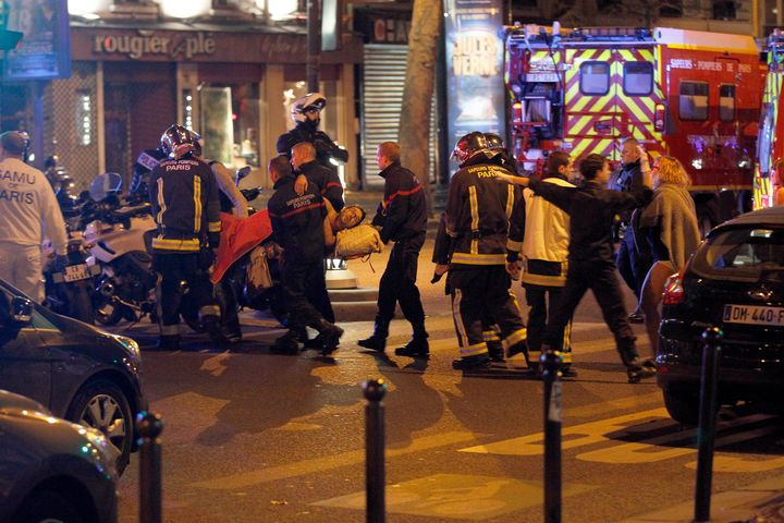 Medics move a wounded man near the Boulevard des Filles-du-Calvaire after an attack November 13, 2015 in Paris, France. (Thie