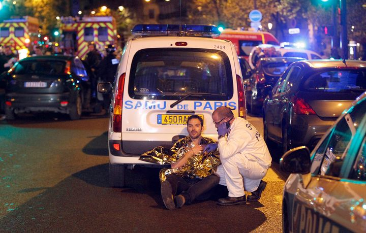 A medic tends to a man November 13, 2015 in Paris, France. Gunfire and explosions in multiple locations erupted in the French