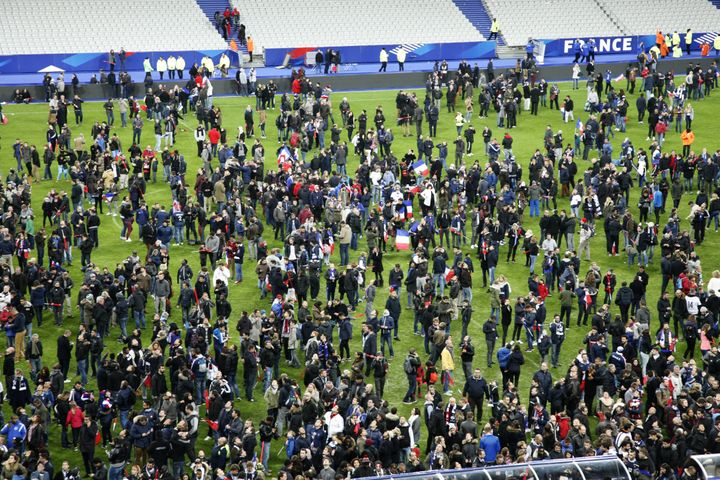 Spectators wait on the pitch of the Stade de France stadium in Seine-Saint-Denis, Paris' suburb on November 13, 2015 after a