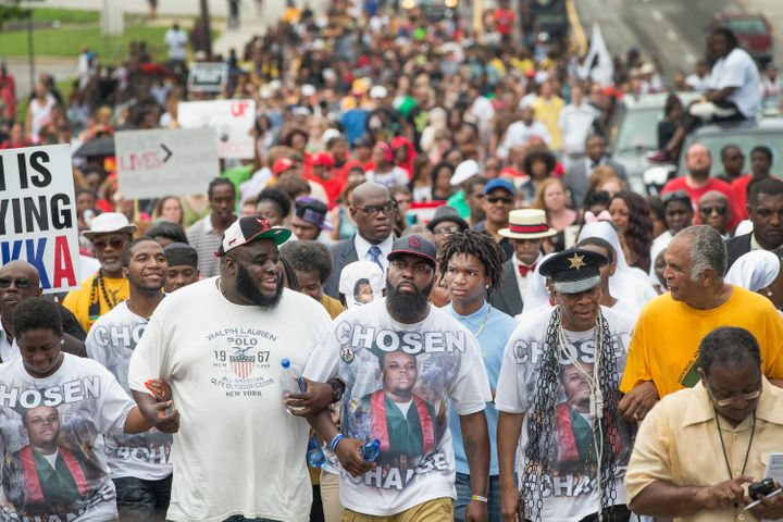 Michael Brown Sr. (center, front) leads a march marking the anniversary of his son's death on Aug. 9, 2015. The photo on his