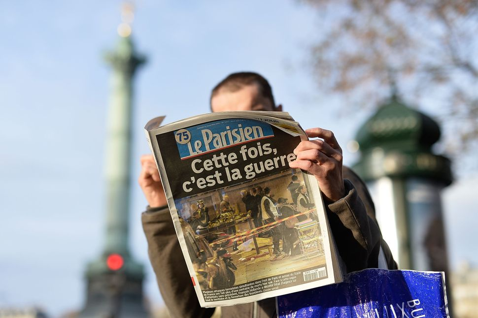 "A man reads a French newspaper with the front-page headline ""This time, it's war"" after a terrorist attack on November 14, 20"