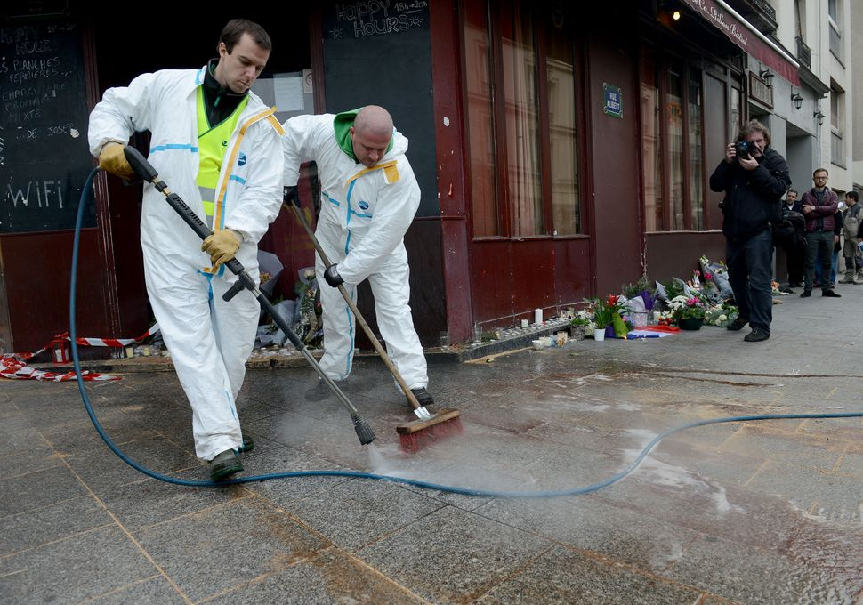 Municipal employees clean the blood outside Le Carillon bar on Nov. 14, 2015, the day after a deadly attack in Paris, Fr